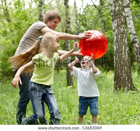 Outdoor happy family with children plaing ball  on green grass.