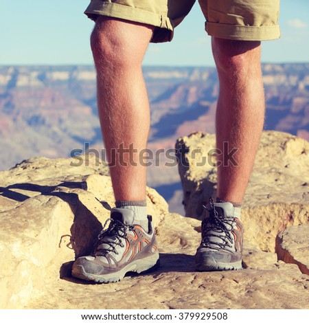 Outdoor hiking shoes - closeup crop of legs of male hiker walking in wool socks and boots on summer nature trail, grand canyon background. Active lifestyle adventure gear concept.