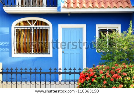 Outdoor image of a typical Dominican house with colorful flowerbed in front of it - stock photo