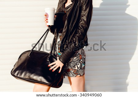outdoor image of stylish woman with total black outfit,leather suit,trendy coat,fall fashion bag,girl resting and drinking tea sitting in autumn garden on the steps, wrapped in a woolen plaid blanket. - stock photo