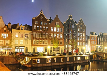 Outdoor landscape with old houses and boats near the canal with reflections in Amsterdam, The Netherlands.