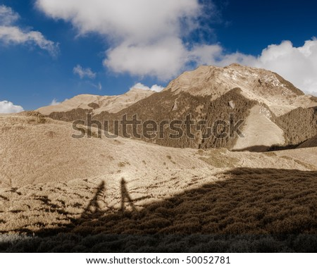 Outdoor landscape with shadow of cameraman and clouds in sky.
