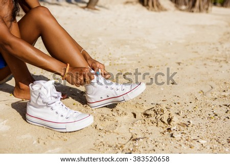 Outdoor lifestyle close-up of the legs of black beautiful teenage girl. Young hipster woman tying laces in her white sneakers. Sunny hot summer day at tropical seashore. - stock photo