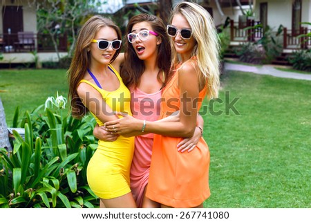 Outdoor lifestyle fashion portrait of the pretty girls friends having fun on vacation, wearing stylish bright neon dresses and sunglasses. Hugs and smiling. - stock photo