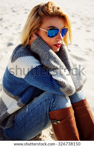 Outdoor lifestyle fashion portrait young pretty blonde girl, wearing stylish  warm sweater,high beige leather boots and sunglasses.Sitting on the sand, basking in the sun. Autumn style, romantic mood  - stock photo