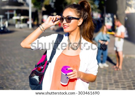 Outdoor lifestyle funny and sunny portrait of young stylish hipster girl walking on street,smiling and laughing on the city,wearing cute trendy outfit,drinking hot latte,travel with backpack,coffee - stock photo