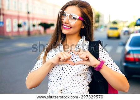 Outdoor lifestyle hipster teen girl posing alone at city center, long amazing hairs, pretty smile, bright make up, travel in Europe with backpack. imitate hear by her hands. - stock photo