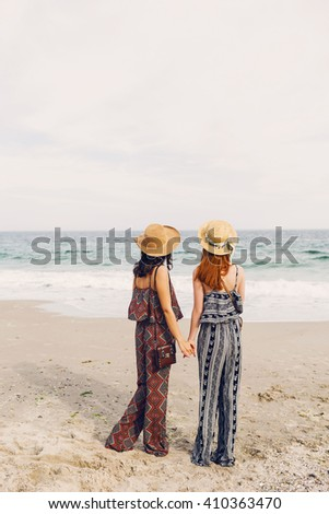 Outdoor lifestyle image of two girls best friends  walking on the sea shore looking at camera laughing, talking. Sisters  strolling along a beach. Stylish summer beachwear, straw hat , sunny colors.  - stock photo