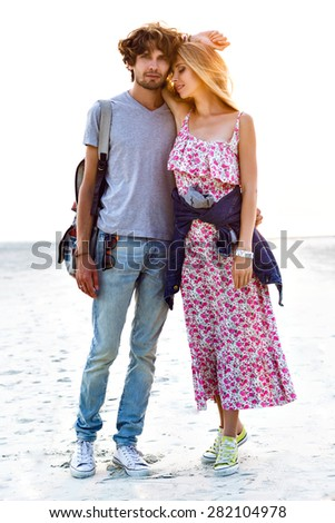 Outdoor lifestyle portrait of amazing pretty hipster young couple in love posing on the beach. Stylish man and woman hugs and spend great time together. floral dress backpack and denim. - stock photo