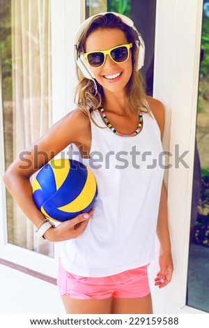 Outdoor lifestyle portrait of amazing pretty smiling young woman, posing in sexy sportive neon shores and sunglasses, listening music in big white earphones and holding ball for game. - stock photo