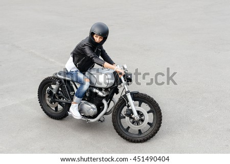 Outdoor lifestyle portrait of biker woman sitting on a vintage custom motorcycle