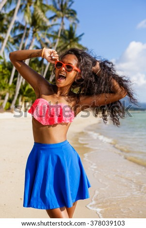 Outdoor lifestyle portrait of black teenage girl in pink bra and blue skirt. Young hipster woman correct her pink sunglasses and happily scream. Sunny hot summer day at tropical beach with palms.
