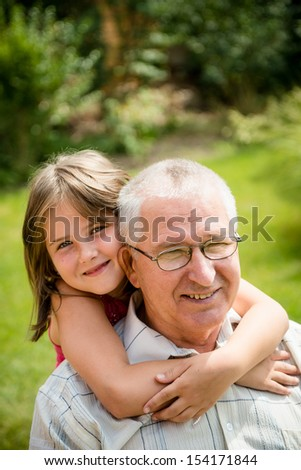 Outdoor lifestyle portrait of grandchild hugging grandfather - stock photo