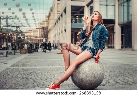 Outdoor lifestyle portrait of pretty young girl blowing bubble in the city, Wearing in hipster swag grunge style urban background. Retro vintage toned image, film simulation. - stock photo