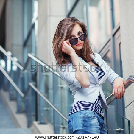 Outdoor lifestyle portrait of pretty young girl posing on stairway, wearing in casual style with sunglasses on urban background. - stock photo