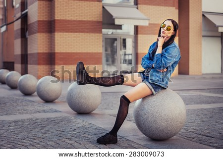 Outdoor lifestyle portrait of pretty young girl, wearing in hipster swag grunge style urban background. Retro vintage toned image, film simulation.