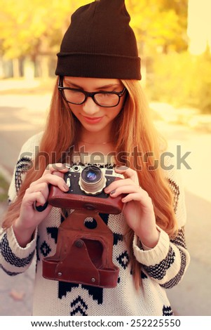 Outdoor lifestyle portrait of pretty young woman having fun with camera travel photo of photographer. Making pictures in hipster style glasses and hat - stock photo