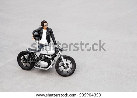 Outdoor lifestyle portrait of sexy biker girl wearing leather jacket and vintage custom motorcycle. Woman get to ride