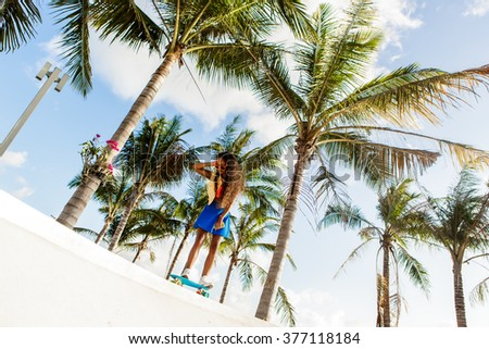 Outdoor lifestyle portrait of sexy black female in bright swimsuit and blue skirt. Hipster lady ride her penny skateboard and her skirt is blown up. She is happy. Sunny summer hot day. Swag, fashion. - stock photo