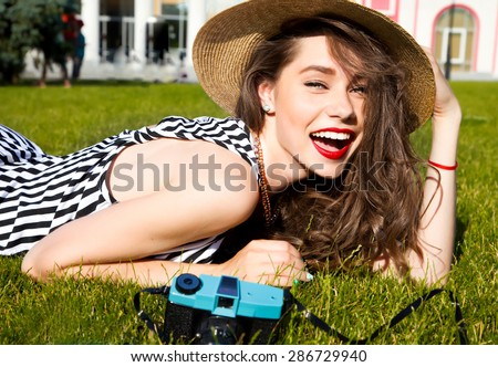 Outdoor lifestyle portrait of stylish girl laughing and smiling holding retro camera.Beautiful sexy woman,evening makeup wearing short dress,summer fall collection perfect in park sun shine,top skirt - stock photo
