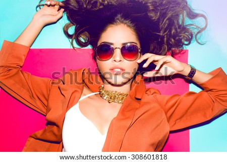 Outdoor lifestyle portrait of teen girl with amazing stylish outfit and sunglasses,leather jacket,white t-shirt,posing on colorful background.fashion accessories,store,amazing autumn colors,toned - stock photo