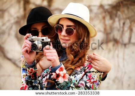 Outdoor lifestyle portrait of two best friends hipsters making photo on their vintage camera, having fun together, joy and happiness, wearing trendy bright clothes and sunglasses. - stock photo