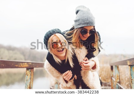 Outdoor lifestyle portrait of two best friends, smiling and having fun together, enjoy each other company posing and making selfie pictures to each other and share happiness  - stock photo
