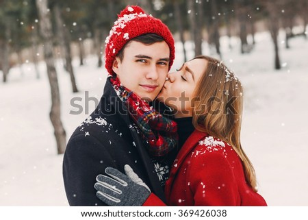 Outdoor lifestyle portrait of young cheerful teen girl and guy  walking in winter time. Hipster couple  in love hugging . Valentines day.  - stock photo