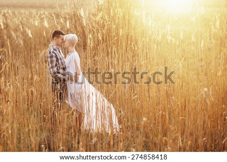 Outdoor lifestyle portrait of young couple hugging on field. Sunny warm weather. Backlight and sunset.  - stock photo