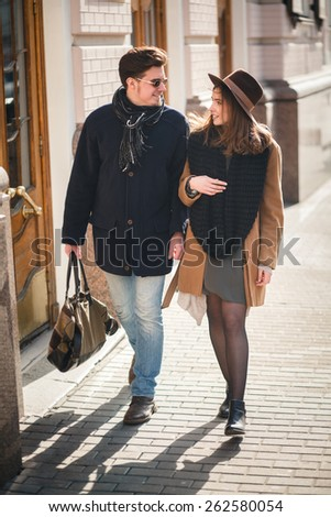 Outdoor lifestyle portrait of young couple in love standing in old town on the street - stock photo