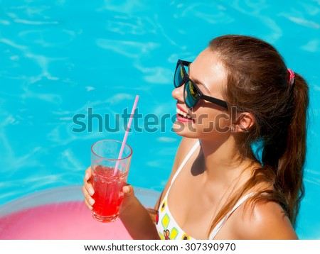 Outdoor lifestyle portrait of young pretty sexy girl swimming with neon bright swimming circle at the pool, wearing bikini and sunglasses, relax and having fun on vacation.Drinking cocktail.Pool party - stock photo