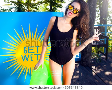 Outdoor lifestyle portrait of young pretty sexy girl swimming with neon bright swimming mattress at the pool,Get wet,pool party,bikini and sunglasses,foam party,wet party,ibiza,kazantip vacation. - stock photo