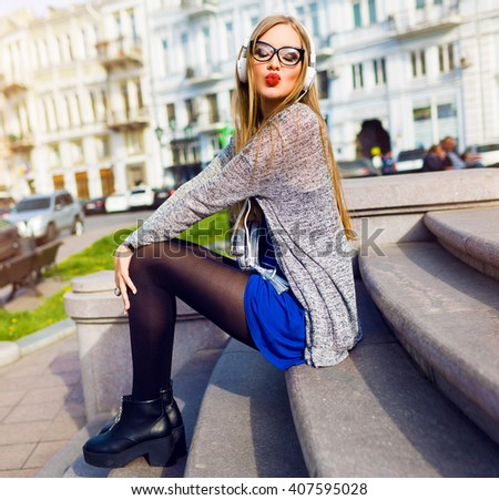 Outdoor lifestyle portrait of young stylish woman with earphones listening to lovely music, send kiss, have fun, enjoying  free time, summer, sunny day.