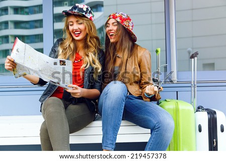 Outdoor lifestyle urban portraits of two playful smiling pretty girls very exited about their trip, screaming smiling and looking to the map, best friends whiting for flight with hand luggage. - stock photo