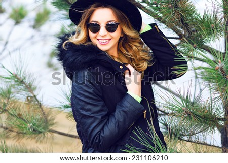 Outdoor lifestyle winter portrait of pretty playful smiling girl posing near spruce wearing vintage sunglasses retro hat and trendy parka. - stock photo