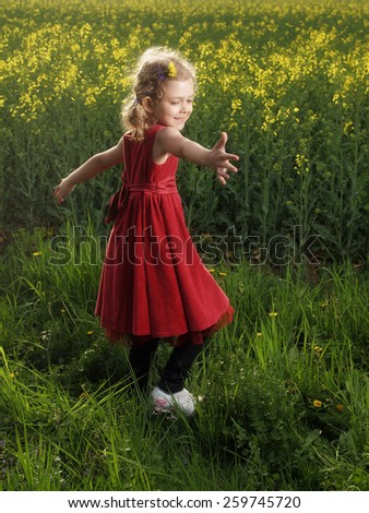 Outdoor little girl dancing on a grass - stock photo
