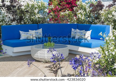 Outdoor living -  armchairs and table set up in the garden - stock photo