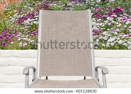 Outdoor lounge chair, colorful daisy flowers and stone wall background. Metal handrest, cloth back and seat.   - stock photo