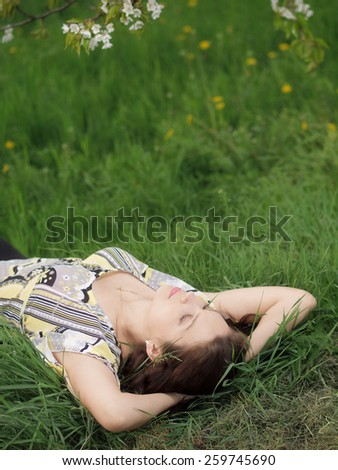 Outdoor lying and dreaming young woman  - stock photo