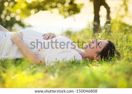 Outdoor natural portrait of beautiful pregnant woman - stock photo
