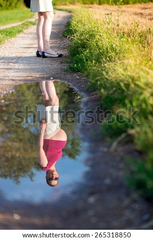 Outdoor natural portrait of beautiful pregnant woman - reflection in the water - stock photo