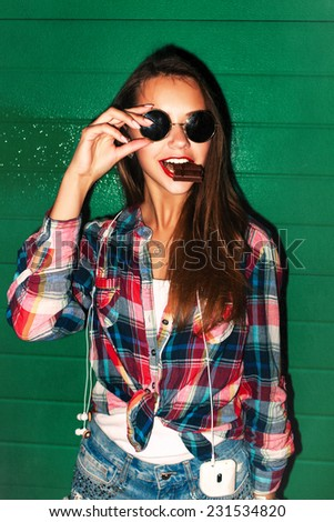 Outdoor night closeup lifestyle urban style portrait of pretty young beautiful girl with smile and chocolate in her mouth with red lipstick having fun wearing round sunglasses  - stock photo