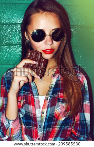 Outdoor night evening dark fashion closeup portrait of nice sensual pretty sexy brunette woman with seductive red lips and chocolate ready to eat and passion dressed vintage hipster style smile  - stock photo