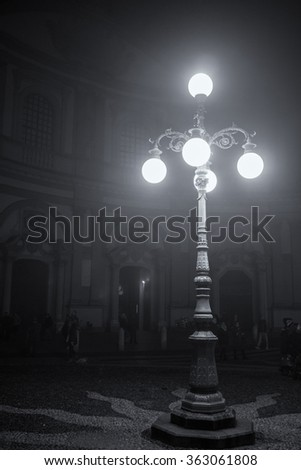 Outdoor night time view of old street lamp in front of a cathedral in Italy during winter time