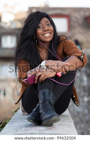 Outdoor of a  portrait happy young african american teenage girl listening to music - stock photo