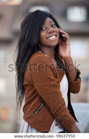 Outdoor of a portrait happy young black  teenage girl using a mobile phone - stock photo