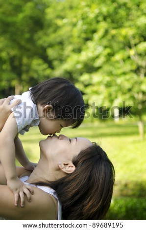 Outdoor park mother kissing son