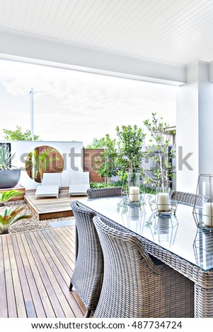 Outdoor patio area with rattan chairs on the wooden floor next to the glass panel table, there are candle beside the garden ground with stones, there are chairs in the relaxing area with trees