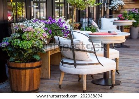 Outdoor patio seating are with nice armchair sofa, potted plants, flower at sunset - stock photo