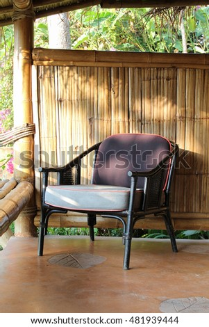 Outdoor patio seating area in bamboo house with brown rattan chair.